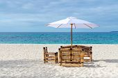 stock photo of boracay  - Tropical beach resort view with turquoise sea lonely beach table with chairs from bamboo and umbrella on exotic white sandy Puka beach on Boracay Philippines - JPG