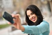 stock photo of braces  - Portrait of a beautiful young woman using braces selfie in the street with a smartphone - JPG