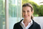 stock photo of jacket  - Close up portrait of a smiling business woman with black jacket and white shirt standing outside - JPG