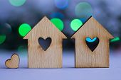 pic of two hearts  - Two wooden houses with hole in the form of heart with little heart on blue and green bokeh background - JPG
