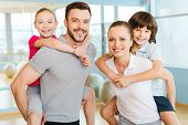 foto of bonding  - Happy sporty family bonding to each other while standing in sports club together - JPG