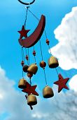 pic of moon stars  - Moon and stars wind chimes with blue sky background.