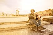 foto of rasta  - young rasta guy outdoor sitting on his skateboard with a warm filter applied - JPG