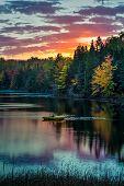 image of sleepy  - The sun rises over a sleepy Michigan lake with swimming platform - JPG