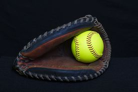 stock photo of fastpitch  - A fastpitch mitt with a yellow ball - JPG