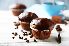 stock photo of chocolate muffin  - Tasty homemade chocolate muffins and cup of coffee on wooden table - JPG