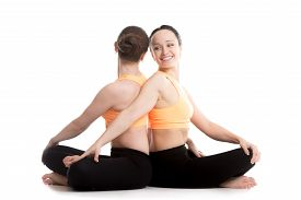 foto of pranayama  - Two smiling girls in orange sportswear on white background doing acroyoga yoga with partner Sitting in Easy  - JPG