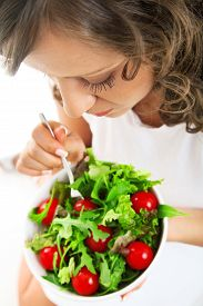 foto of youg  - Youg woman eating healthy salad isolated on white background - JPG