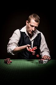 picture of gambler  - A male gambler rolls the dice after the betting - JPG