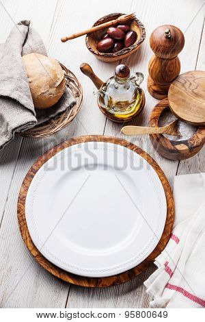 White Empty Plate And Olive Wood Tableware On White Wooden Background