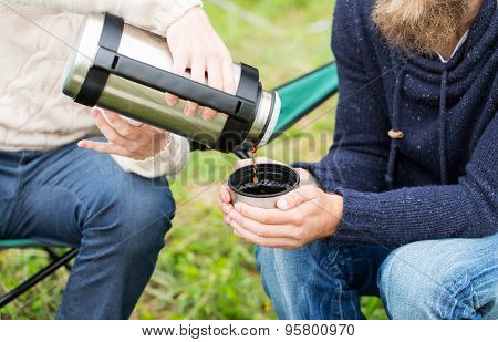 adventure, travel, tourism and people concept - close up of male hikers pouring tea from thermos to cup outdoors