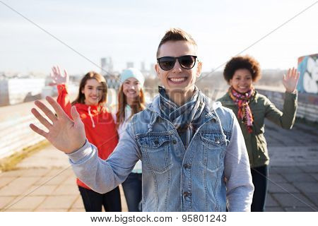 people, friendship and international concept - happy african american young man or teenage boy in front of his friends waving hands on city street