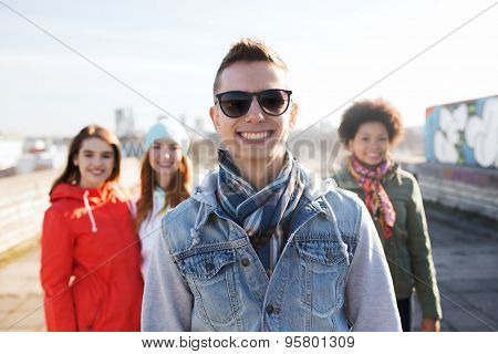 people, friendship and international concept - happy young man or teenage boy in front of his friends on city street