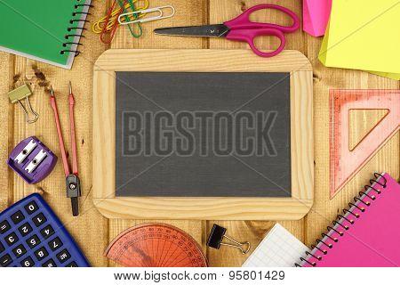 Blank chalkboard with school supplies on wood