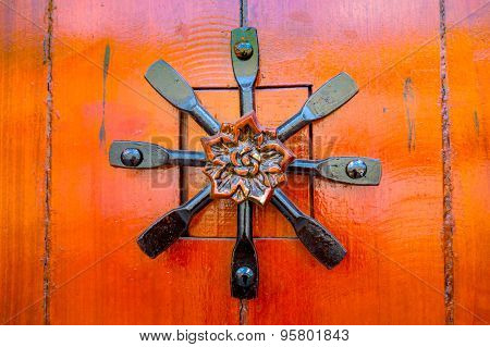Door handle with four pieces of black metal crossing each other shaping a fan formation and wooden c
