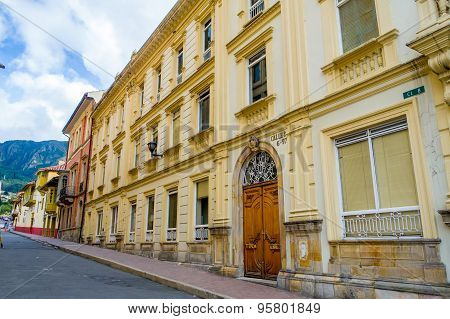 Very nice yellow colored concrete architectural facade of old townhouse with double sided wooden ent