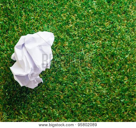 Crumpled paper on Green yard grass background
