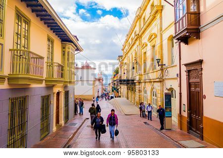 Typical charming street in old part of Bogota with people walking on red stoned pavements sorrounded