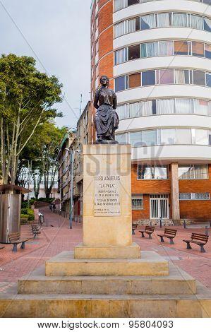 Bronze statue honoring Colombian heroine Policarpa Salavarrieta aka La Pola in front of modern apart