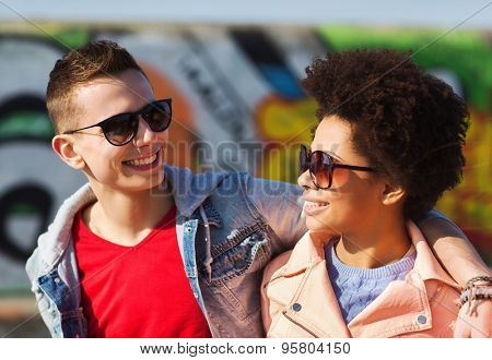 friendship, tourism, trave, relations and people concept - group of happy teenage friends in sunglasses hugging outdoors