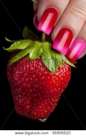 Fingers with beautiful manicure hold juicy strawberries.