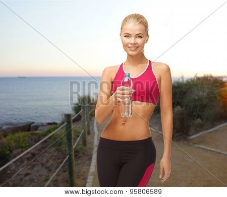 people, sport, fitness, jogging and recreation concept - happy woman with bottle of water over beach sunset background