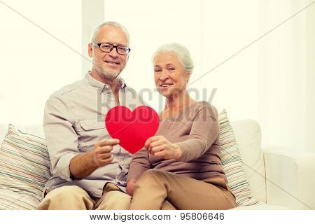 family, holidays, age and people concept - happy senior couple with little red paper heart shape cutout at home