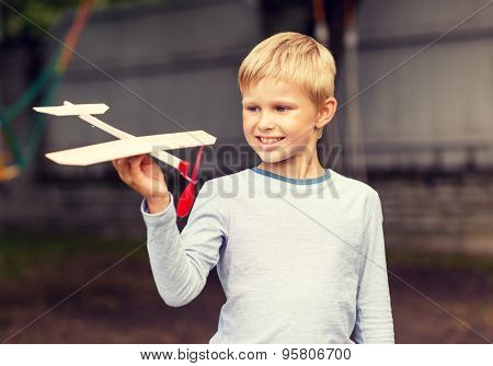 dreams, future, hobby, people and childhood concept - smiling little boy holding wooden airplane model in his hand outdoors