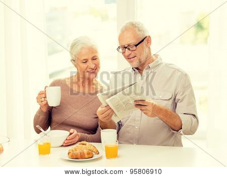 family, technology, food, drinks and people concept - happy senior couple having breakfast and reading newspaper at home