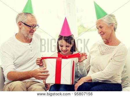 family, generation, holidays and people concept - smiling grandfather, granddaughter and grandmother in party hats with gift box at home