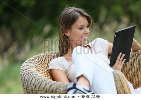 Woman relaxing in outdoor armchair and using digital tablet