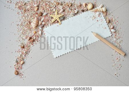 Sea shells, pink sand and invitation card with a pencil on a paper background