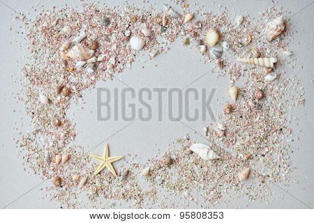 Sea shells and pink sand with a starfish on a paper background with empty space for text