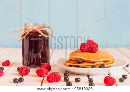 Stack of wheat golden pancakes or pancake cake with freshly picked raspberry on a dessert plate, gla