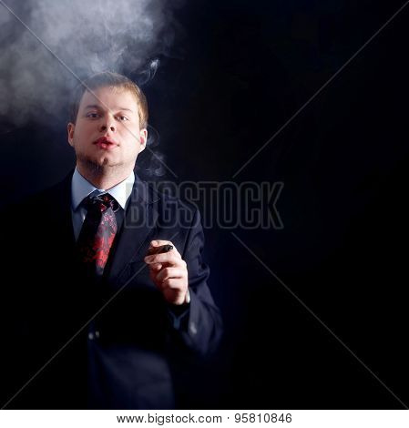 The man in costume smoke a cigar, looks at us. lots of smoke. A dark background