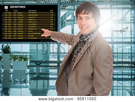 Business man at the airport terminal in front of the departure board