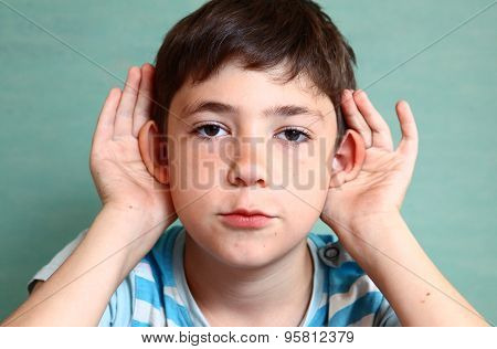 Preteen Beautiful Boy Hold His Hear Isolated On Blue