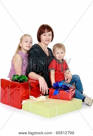 happy family sits surrounded by gifts mother's eldest daughter and young son