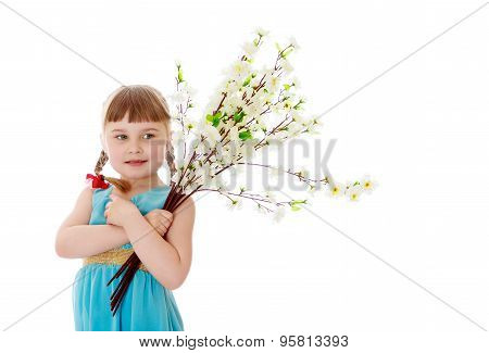 Adorable little blonde girl with short bangs and braids which are plaited red bows , in a long blue