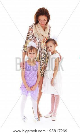 Happy family, a slim beautiful young mother tenderly embracing their 2 beloved daughters