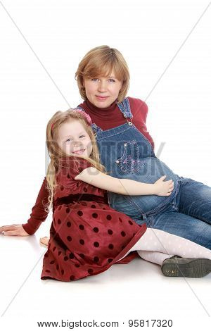 Happy little blonde girl in a long brown dress with polka dots hand stroking the belly of his belove