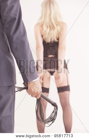 Leather whip held by dominant master in suit