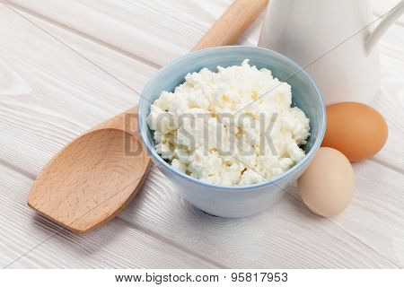 Dairy products on wooden table. Curd, eggs and milk
