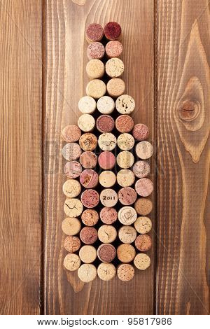 Wine bottle shaped corks over rustic wooden table background. View from above
