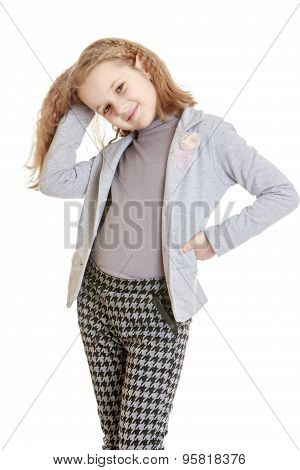 Stylish young blonde girl in a pantsuit moves his hands up her long hair