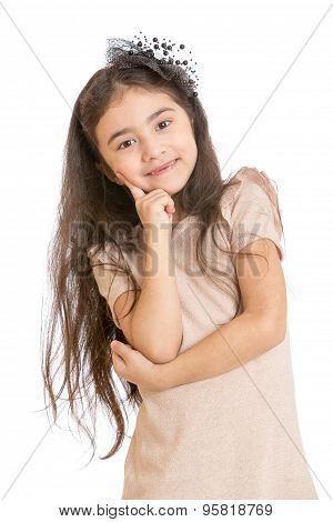 Fashionable little girl with long dark hair and beautiful barrette on her head posing for the camera