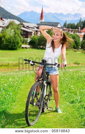 Happy woman biking along cute little mountainous village, enjoying sport outdoors, bicycle tour in the Alps, Austria, Europe