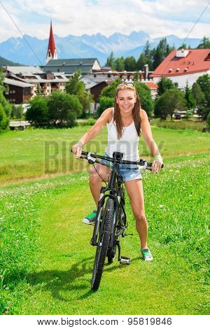 Happy woman riding on bicycle along cute little mountainous village, doing sport exercise outdoors, bikers tour in the Alps, Austria, Europe