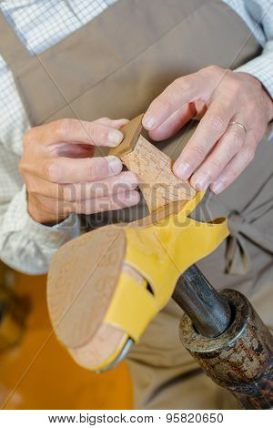 cobbler mending heel of shoe