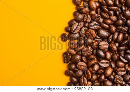 Roasted coffee beans close up. Yellow background. Space for text.